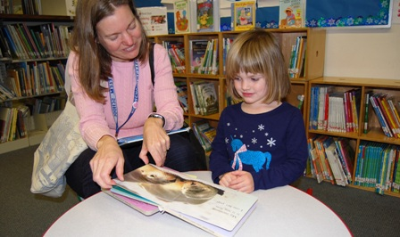 Mother and preschool daughter reading board book